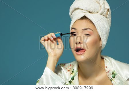 young attractive woman putting eye mascara over blue background, beauty treatment morning