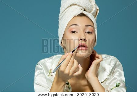 young attractive girl putting lipstick on lips over blue background, beauty treatment morning