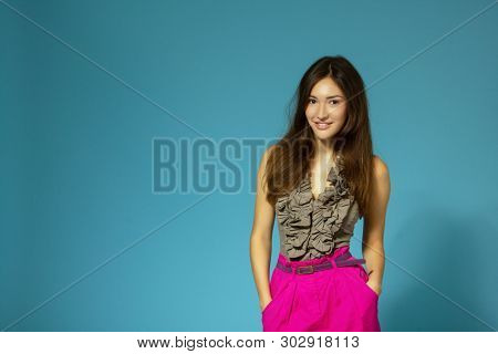 Beautiful cheerful teen girl, isolated over blue background. Young pretty woman posing at studio, copy space
