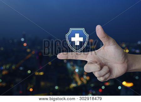Cross Shape With Shield Flat Icon On Finger Over Blur Colorful Night Light City Tower And Skyscraper