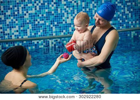 Happy Smiling Baby Boy And His Young Mother Standing In Paddling Swimming Pool. Infant In Moms Hands