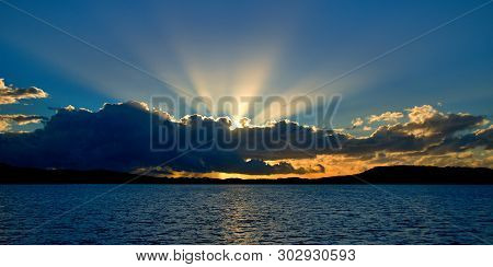 A Stormy Radiating Crepuscular Rays Blue,grey And White Coloured Cumulonimbus Cloudy Sunrise Seascap