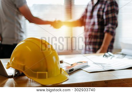 Yellow Safety Helmet On Workplace Desk With Construction Worker Team Hands Shaking Greeting Start Up