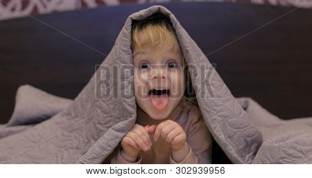 Little Cheerful Girl Hides Under A Blanket And Watching Tv. Sweet, Adorable Child Having Fun On The