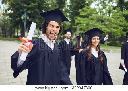 Man Graduate Is Smiling Against The Background Of University Graduates.