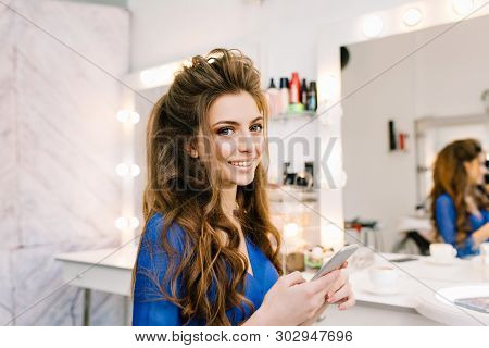 Pretty cute young woman with long brunette hair smiling to camera in hairdresser salon. Beauty, preparing to party, celebration, luxury lifestyle, happiness, true positive emotions, coiffure. poster