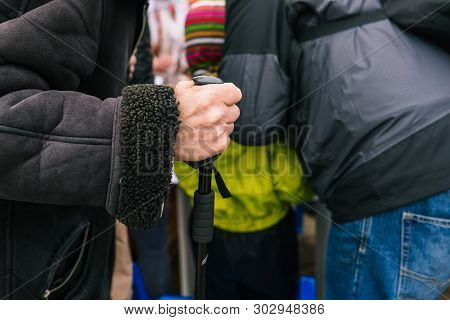 The Hand Of An Elderly Man With A Cane. An Old Man Leans On A Stick. Beggar Pedestrian On The Street