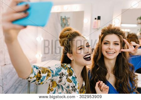 Stylish portrait two stylish attractive models with stylish makeups, luxury coiffures making selfie in hairdresser salon. Friends together, having fun, expressing true positive emotions, beauty. poster