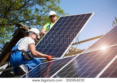Two Professional Technicians Adjusting Heavy Solar Photo Voltaic Panels To High Steel Platform. Exte