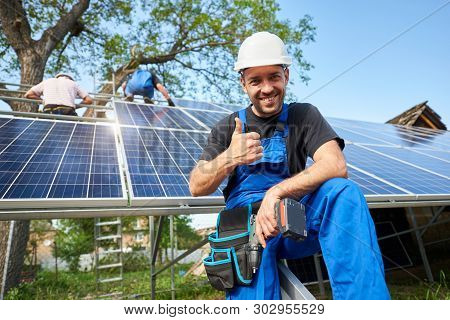 Portrait Of Smiling Technician With Electrical Screwdriver Showing Thumb-up In Front Of Unfinished H