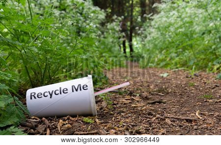A discarded drink cup lies at the side of a forest track despite having recycle me written on it poster