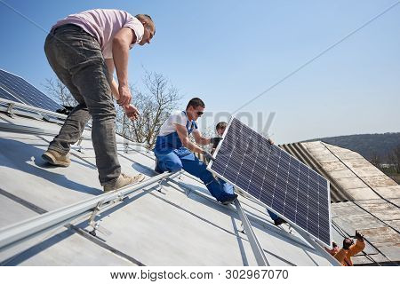 Male Engineers Installing Solar Photovoltaic Panel System. Electricians Lifting Blue Solar Module On