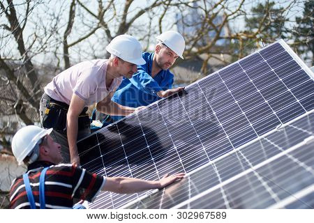 Male Team Workers Installing Solar Photovoltaic Panel System. Three Electricians Mounting Blue Solar