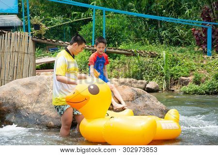 Two Boy Prepare To Jump On Plastic Duck Balloon To Row Downstream