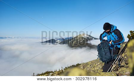 Tourist Hiker With Trekking Poles Looking In Backpack On Steep Rocky Mountain Slope On Background Of