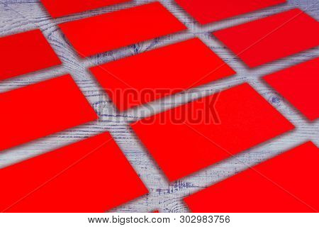 Mockup Of Horizontal Red Business Cards Stacks Arranged In Rows At Purple, Blue Wooden Background.