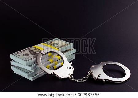Money And Handcuffs. Financial Crime  Card Fraud  Counterfeit Cards Fake Check Scams  Concept