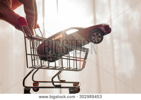 Red Toy Car In Shopping Cart. Cheap Used Cars, Sell A Car Concept. Daylight Background