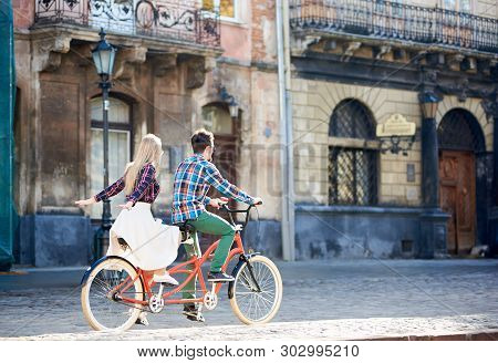 Back View Of Young Tourist Couple, Bearded Man And Long-haired Blond Woman In White Skirt Riding Tan