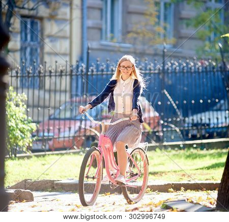 Young Attractive Smiling Blond Woman In Glasses, White Blouse And Skirt Riding Pink Lady Bike Along