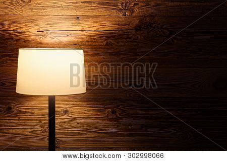 Indoor Scene Of A Floor Lamp Against Wooden Wall. Torfhaus, Germany