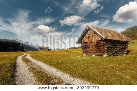 Incredible Bavarian Alps. View On Fairy Alpine Valley With Tipical Wooden Huts, With Zugspitze Mount