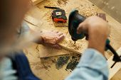 Above view of unrecognizable carpenter drilling wood while working in joinery, copy space poster