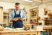 Waist up portrait of senior carpenter using tablet while working in joinery, copy space poster