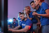 Young people playing video games on computers indoors. Esports tournament poster