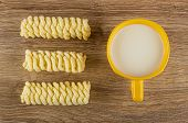 Pieces of cornflake pigtails, yellow cup with milk on wooden table. Top view poster