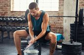 Fitness young man rubbing hands with chalk magnesium powder. Determined muscular guy preparing for weight lifting in gymnasium. Man clapping hands and preparing for workout at crossfit club. poster