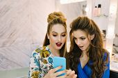 Portrait two astonished pretty women looking at phone in beauty salon. Having fun, gossip girls, preparing to party,  friends together, true emotions, professional makeup, coiffure, stylish models. poster