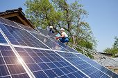 Two technicians on metal platform connecting solar photo voltaic panels on bright sunny day. Stand-alone solar panel system installation, efficiency and professionalism concept. poster