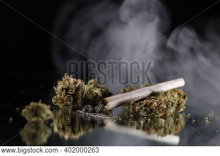 Cannabis Branch And Joint In The Smoke On A Black Background. Marijuana Legalization. Medical Cannab