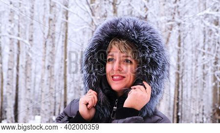 Winter Portrait Of A Young Beautiful Brunette Woman In A Winter Jacket With Fur. Snow Winter Beauty