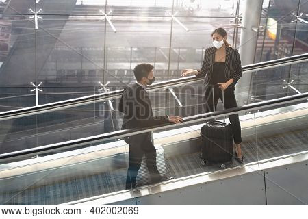 Business People Wearing Face Mask Walking On Escalator At The Airport. New Normal Safety Business Tr