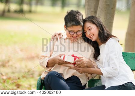 Young Beautiful Asian Woman Smiling And Gives Warm Hug With A Present To Her Mom In The Park As A Ba