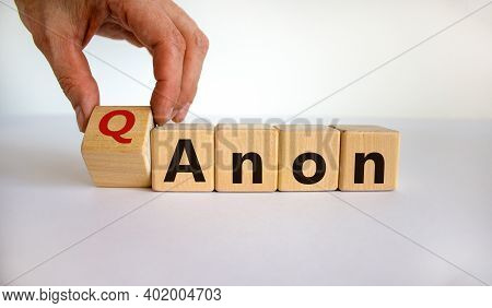Q Anon Symbol. Male Hand Turns A Wooden Cubes And Changes The Word 'anon' To 'qanon'. Beautiful Whit