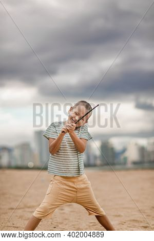 Outdoor portrait of a little cute boy with stick