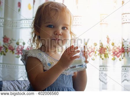 Little Toddler Girl Child Drinks From A Glass Goat Or Cow Milk, Natural Rustic. The Happy Kid Smiles