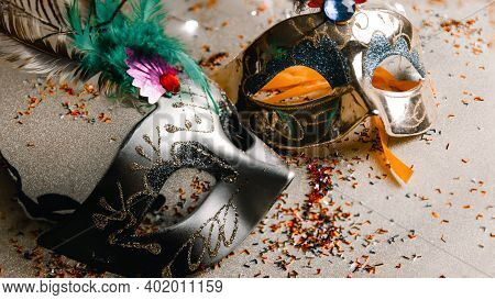 Shot Of Two Venetian Masks, One Silver And One Gold, On A Gold Background With Sparkling Lights And