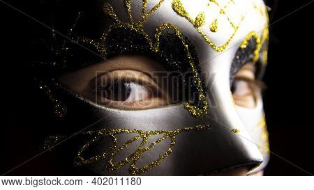 Close-up Of A Girl's Eyes With A Silver And Gold Mask. Carnival And Mystery Concept.