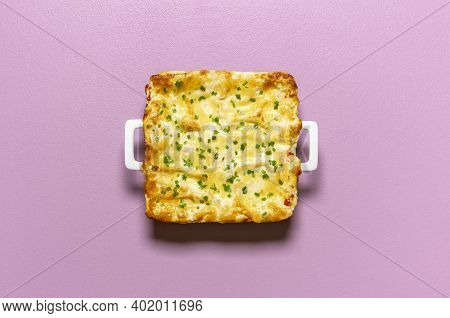 Vegetable Lasagna Tray With Melted Cheese, Isolated On A Purple Background. Flat Lay With Freshly Ba