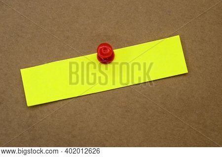 One Yellow Paper Sheet Is Attached With A Red Office Button On A Brown Background. Concept Photo