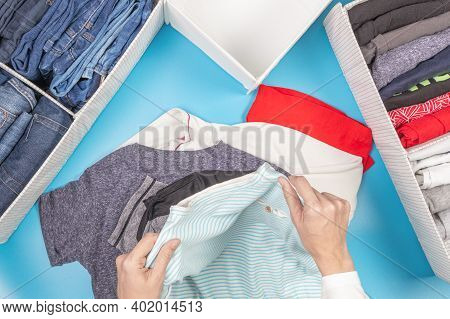 Female Hands Folds And Puts Clothes To Baskets. Vertical Storage Of Clothing, Tidying Up, Room Clean
