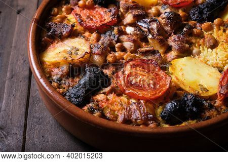 Close-up Of Clay Pot Of Baked Rice With Tomato, Potato And Black Pudding.