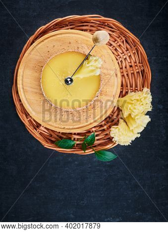 Tete De Moine Cheese On The Device Cheese Cutter And On A Braided Basket On A Dark Background, Shall