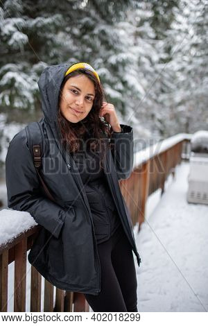 Woman Leaning Against Snow-covered Handrail With Snowy Pines As Background