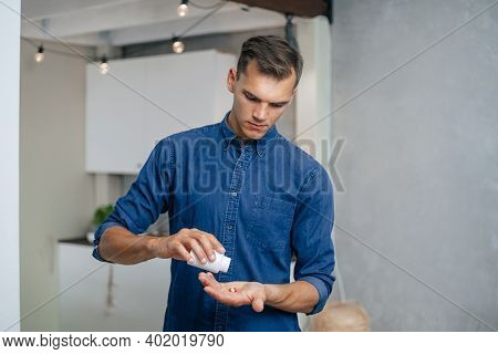 Close Up. Young Man Taking Pills In His Home.