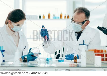 Scientist And Laboratory Assistant Conduct Research In The Laboratory.